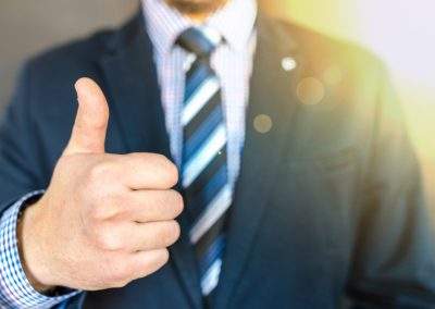 close up photo of man wearing black suit jacket doing thumbs 684385